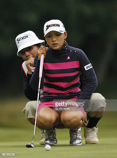 Japanese golfer Sakura Yokomine lines up her putt on the 5th green with the help of her caddie during the first round of the Ricoh Women's British...