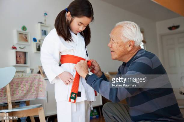Japanese grandfather helping granddaughter with karate uniform