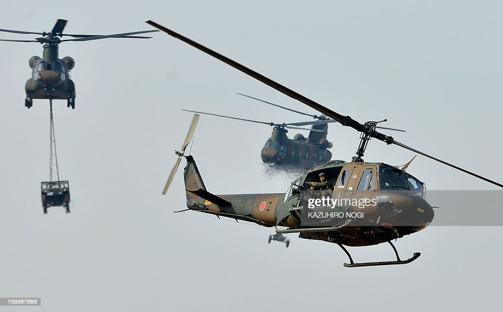 Japanese Ground Self Defense Force helicopters fly over ground troops taking part in a new year military drill at the training grounds in Narashino, suburban Tokyo on January 13, 2013. A total of 300 personnel, 20 aircraft and 33 vehicles took part in the open exercise at the defense force's Narashino training ground.
