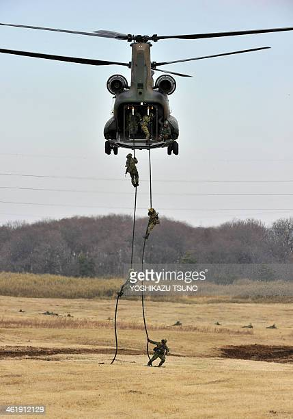 Japanese Ground Self Defense forces' airbourne troop personnel jump from a CH47 helicopter during the new year exercise in Narashino in Chiba...