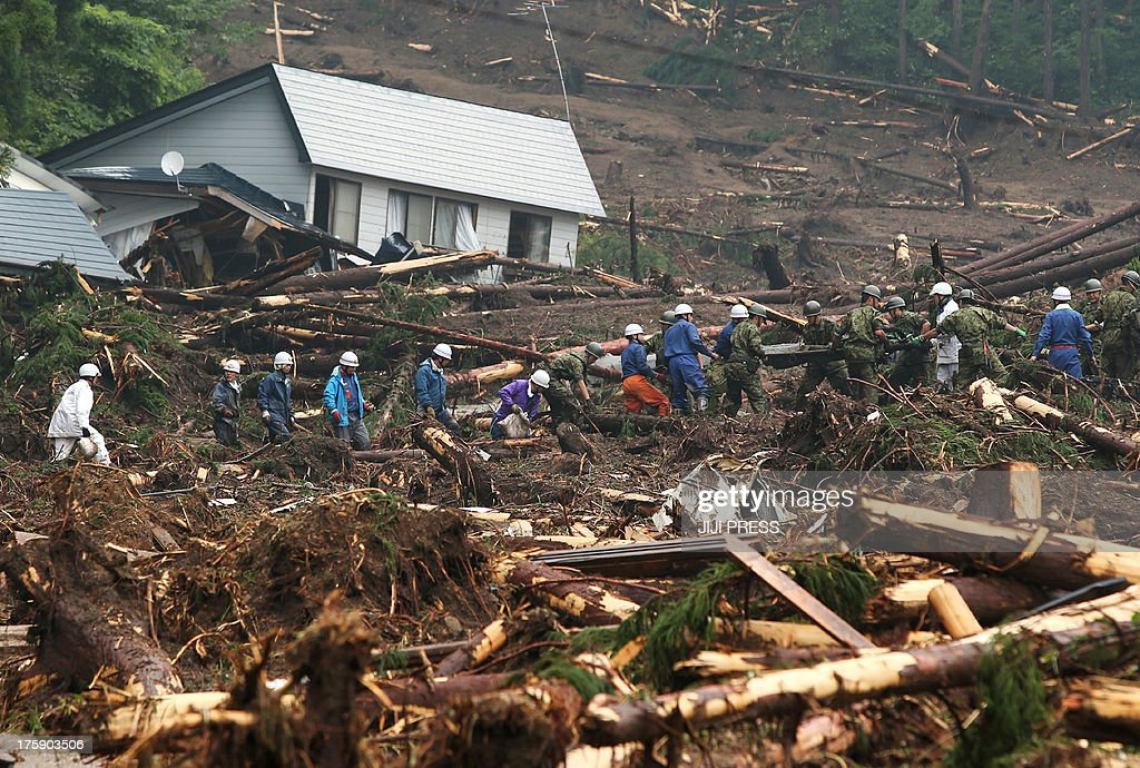 Japanese Ground Self Defense Froces carry a stretcher amongst debris as they search for victims following floods near Lake Tazawa in Semboku, Akita prefecture on August 10, 2013. Two people were killed and five others missing on August 9 as torrential rain hit northern Japan, local media reported. AFP PHOTO / JIJI PRESS --JAPAN OUT--