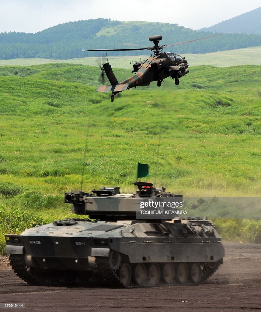 Japanese Ground Self-Defense Forces AH64D helicopter takes a position as a type-89 armored fighting vehicle moves during an annual live fire exercise at the Higashi-Fuji firing range in Gotemba, at the foot of Mt. Fuji in Shizuoka prefecture on August 20, 2013. The annual drill involves some 2,400 personnel, 80 tanks and armoured vehicles and 30 aircraft and helicopters.