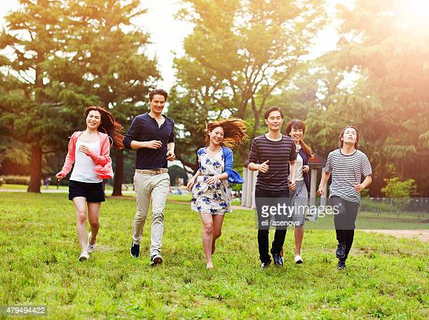Japanese group young friends running together in the park, Tokyo.