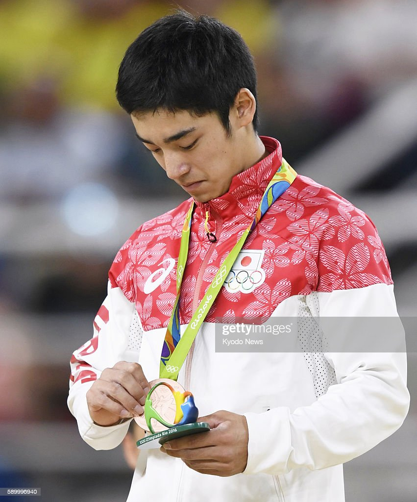 Japanese gymnast Kenzo Shirai looks at his bronze medal at the awards ceremony for the men's vault after finishing third in the final at the Rio de...