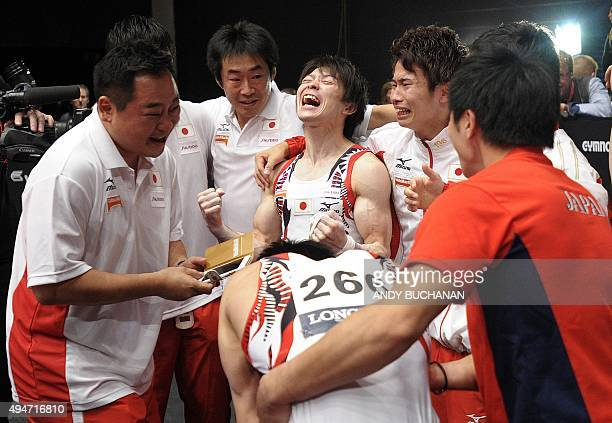 Japanese gymnast Kohei Uchimura celebrates with his team mates after Japan won the gold medal during the Men's Team event final on the sixth day of...