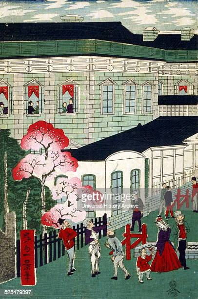 Japanese hand coloured woodcut Image shows a street scene in which Japanese people are gathered outside the trainstation The passengers are shown...