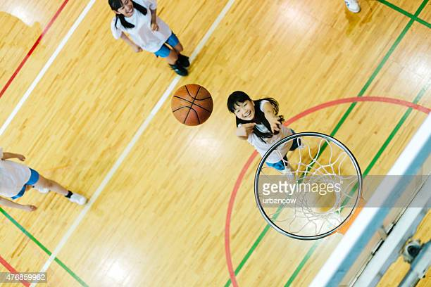 Japanese high school. A school gymnasium. Children play basketball