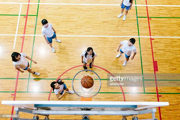 Japanese high school. A school gymnasium. Female students play basketball