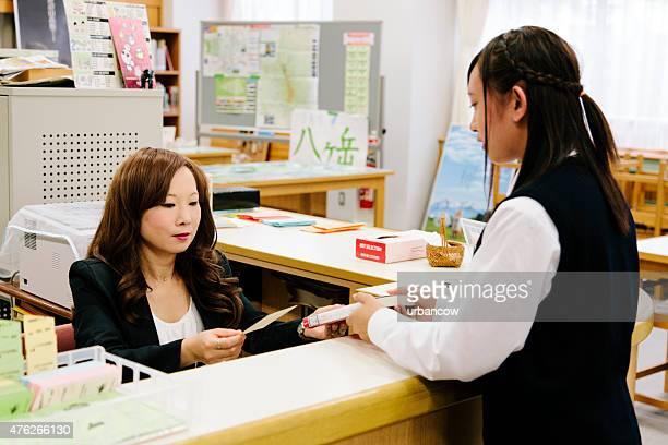 Japonais high school, empruntant un livre, étudiante et Bibliothécaire