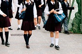 A view of a Japanese high school. Students, in school uniform, walk together outside their school building. Exterior view, horizontal composition, neck down, unrecognisable.