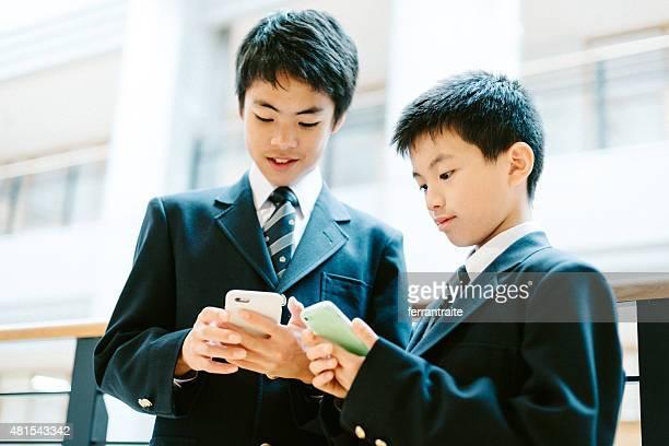 Japanische High-school-Schüler in der Schule mit Smartphones