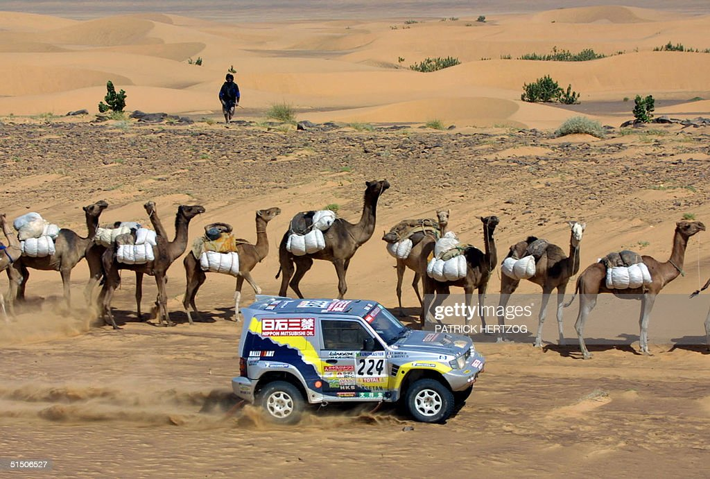 Japanese Hiroshi Masuoka in a Mitsubishi passes a camel caravan, in the maurtanian desert 16 January 2001 during the Tichit-Nema stage of the Paris-Dakar Rally. Masuoka won the special stage and also is in overall lead ahead of French Jean-Louis Schlesser.