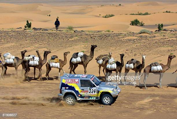 Japanese Hiroshi Masuoka in a Mitsubishi passes a camel caravan in the maurtanian desert 16 January 2001 during the TichitNema stage of the...
