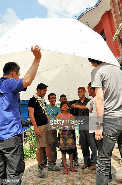 Japanese including its architect Yusuke Murakami display how to erect the tent on May 11 2015 in Bungamati Nepal The white domeshaped shelter...