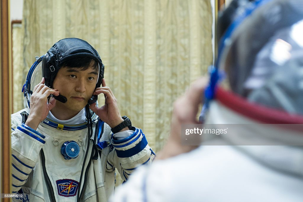 Japanese JAXA astronaut Takuya Onishi is reflected in a mirror as he attends a training session at the Gagarin Cosmonauts' Training Centre in Star City, outside Moscow, on May 24, 2016. Members of the International space crew, Russian cosmonaut Anatoli Ivanishin, Japanese JAXA astronaut Takuya Onishi and US NASA astronaut Kate Rubins are to take off from Kazakhstan's Baikonur cosmodrome to the International Space Station (ISS) on June 24, 2016. / AFP / -