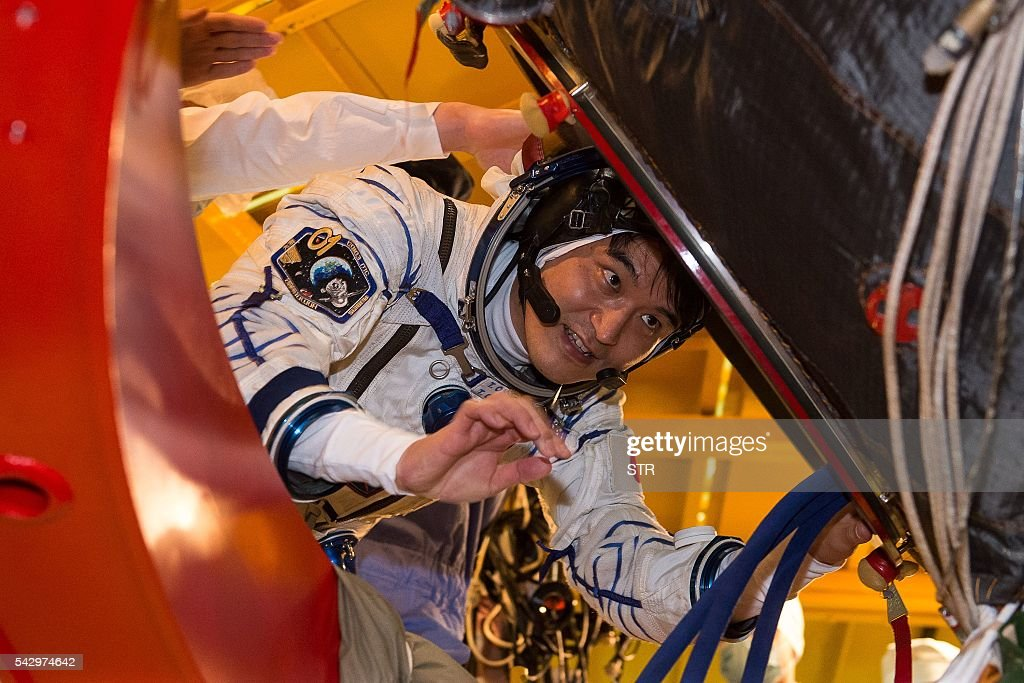 Japanese JAXA astronaut Takuya Onishi, member of the main crew of the 48/49 expedition to the International Space Station (ISS), gets into the Soyuz MS01 space vehicle in an assembling department at the Russian-leased Baikonur cosmodrome in Kazakhstan on June 25, 2016. The trio is to take off from Kazakhstan's Baikonur cosmodrome to the International Space Station (ISS) on July 7, 2016 / AFP / STR