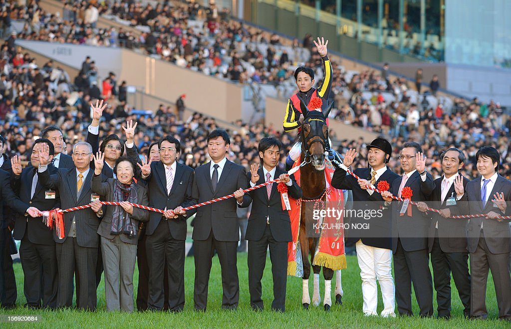 Japanese jockey Yasunari Iwata (C) on Gentildonna celebrates during the awards ceremony of the 2,400-metre (1.5 mile) Japan Cup horse race at the Tokyo Race Course on November 25, 2012. Gentildonna edged past Prix de l'Arc de Triomphe runner-up Orfevre by a nose to become the first three-year-old filly to win the Japan Cup horse racing. AFP PHOTO / KAZUHIRO NOGI