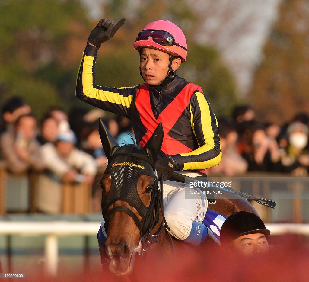 Japanese jockey Yasunari Iwata on Gentildonna reacts after finishing the 2,400-metre (1.5 mile) Japan Cup horse race at the Tokyo Race Course on November 25, 2012. Gentildonna edged past Prix de l'Arc de Triomphe runner-up Orfevre by a nose to become the first three-year-old filly to win the Japan Cup horse racing. AFP PHOTO / KAZUHIRO NOGI
