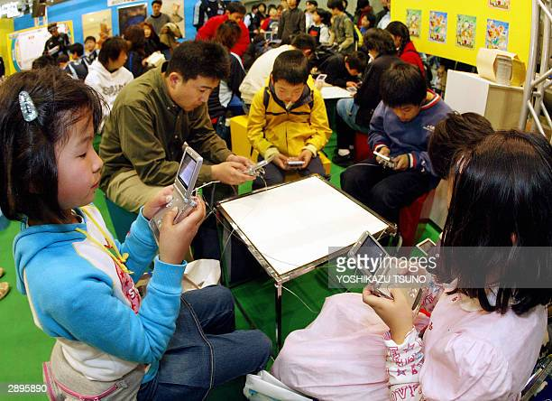 Japanese kids concentrate to play the new soccer game 'Netsal' which will be on sale next spring on Nintendo's portable video game console Gameboy...