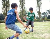 Japanische Kinder spielen Fußball
