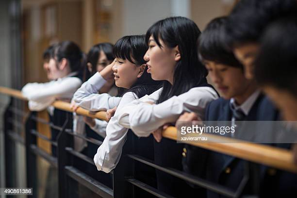 Japanese kids relax on a bannister at school