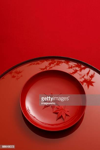 Japanese lacquer ware with maple leaf against red background, close-up