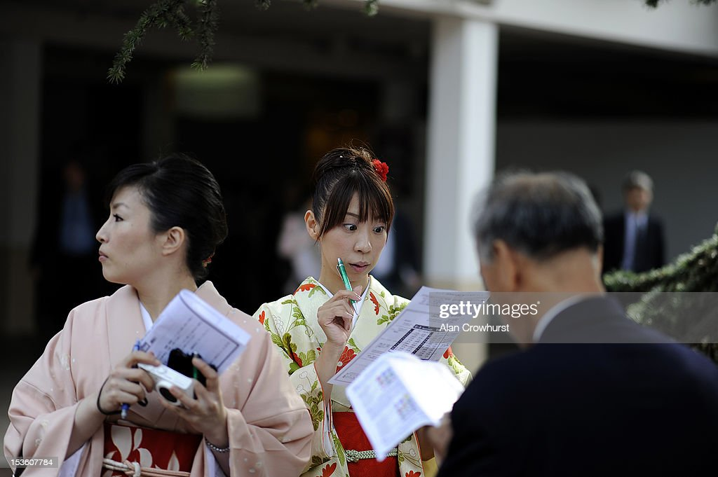 A Japanese lady studies the form at Longchamp racecourse on October 07, 2012 in Paris, France.