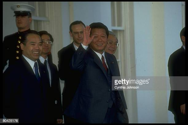 Japanese Liberal Dem Party Secy Gen Ichiro Ozawa waving w entourage in tow leaving WH after mtg w NSC's Scowcroft