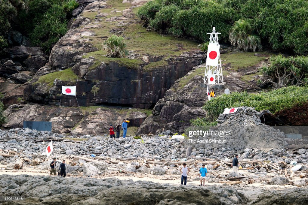Japanese local assembly members raise the Japanese national flag after arriving on Uotsurijima one of the disputed Senkaku or Diaoyu Islands...