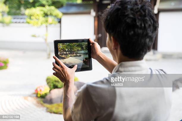 Japanese maan using a digital tablet in a Japanese temple