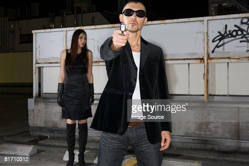 Japanese man aiming gun at camera : Stock Photo