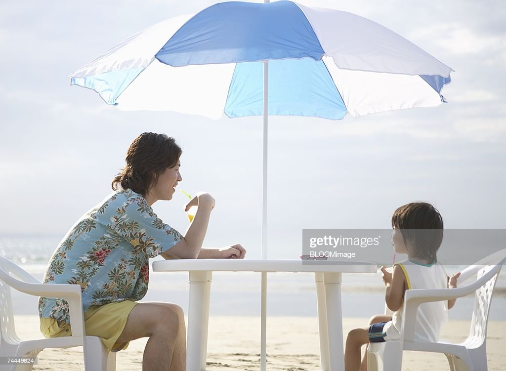 Japanese man and boy sitting on chair under parasol on beach : Stock Photo