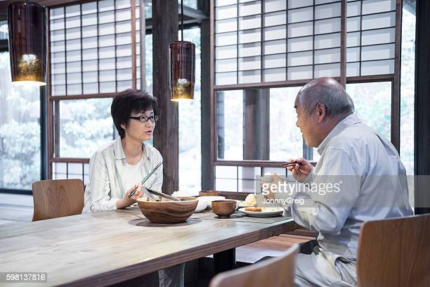 Japanese man and woman sitting at table eating dinner