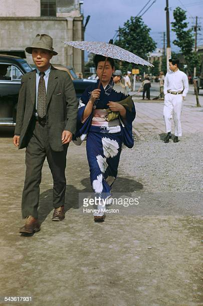 A Japanese man and woman walking on a street in Japan circa 1965