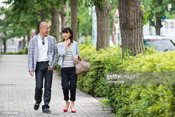 Japanese man and woman walking together down street