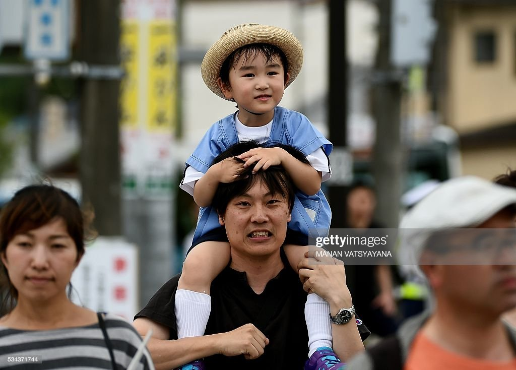 A Japanese man carries his child on his shoulders after the welcoming ceremony of world leaders at Ise-Jingu Shrine in the city of Ise in Mie prefecture, on May 26, 2016 on the first day of the G7 leaders summit. World leaders kicked off two days of G7 talks in Japan on May 26 with the creaky global economy, terrorism, refugees, China's controversial maritime claims, and a possible Brexit headlining their packed agenda. / AFP / MANAN