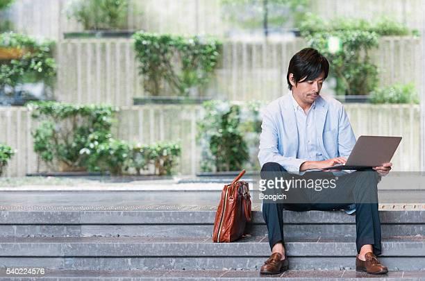 日本の男性とノートパソコンで E メールチェック、オフィスのロビー京都