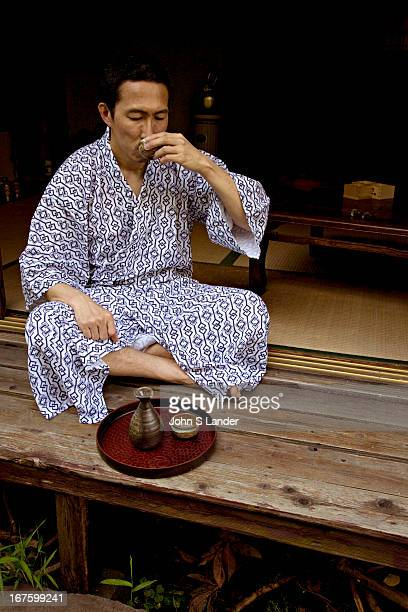 Japanese Man Drinking Sake or Japanese rice wine a popular drink both in and outside of Japan and has enjoyed a resurgence of popularity in Japan as...