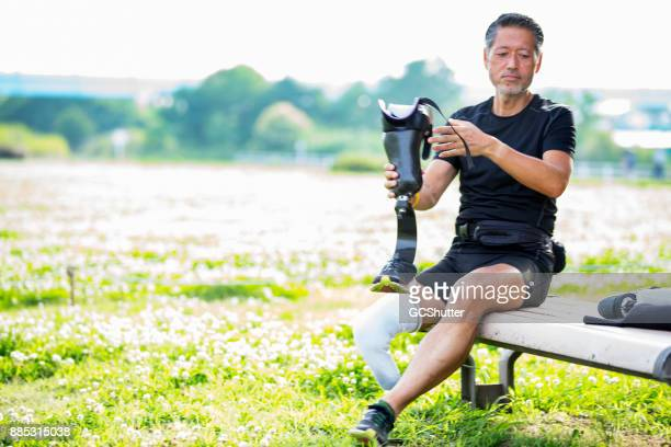 Rotuine ジョギングのための準備の間に彼の義足を保持している日本人の男性