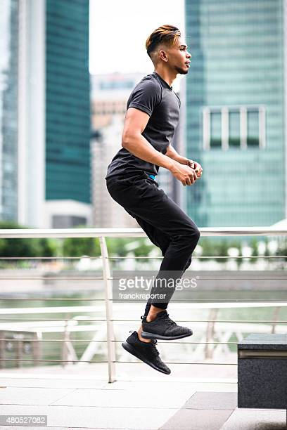 Japanese man jumping high on the city of Singapore