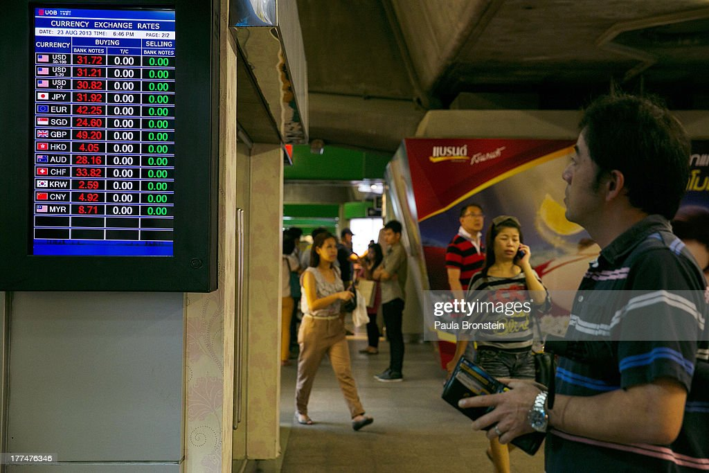 A Japanese man looks at the currency board at a money exchange bank kiosk on August 23, 2013 in downtown Bangkok, Thailand. The local currency dropped to its lowest level since August 2010. Against the US dollar the Thai baht fell to 32.09/32.13 dropping about 5% this year.