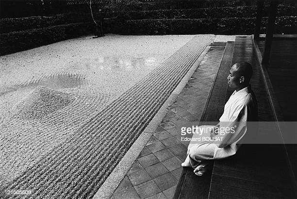 Japanese Man Medidating In Front Of A Zen Garden In Kyoto