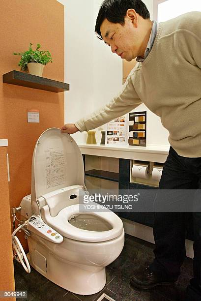 Japanese man opens the cover of a toilet in Tokyo 05 March 2004 A national mania for bathroom hygiene and greater equality between the sexes has...