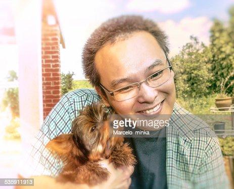 Japonés hombre jugando con perro pequeño. : Foto de stock