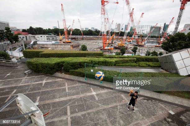 A Japanese man plays basketball at the Tokyo metropolitan gymnasium as the construction site for the National Stadium venue for the upcoming Tokyo...