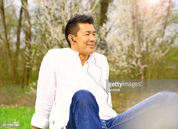 Japanese Man Relaxing and Listening Music on Grass