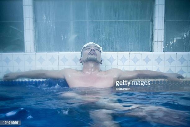 Japanese man relaxing in traditional Onsen bath