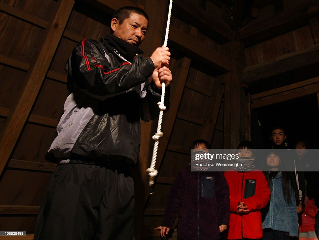A Japanese man rings the bell as others look on at the Sagami-ji Buddhist temple on January 1, 2013 in Kasai, Japan. Japanese people attend the Buddhist temple at midnight on December 31 for the ringing of the temple bell to welcome in the New Year or 'Omisoka' as it is known in Japan. In Japanese belief there are 108 elements to the human mind, so the bell is rung 108 times as a blessing of happiness for the New Year.