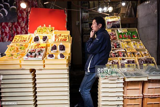 A Japanese man sells fruits at a market in Tokyo on November 1 2016 Japan's central bank again pushed back the timeline for hitting its inflation...