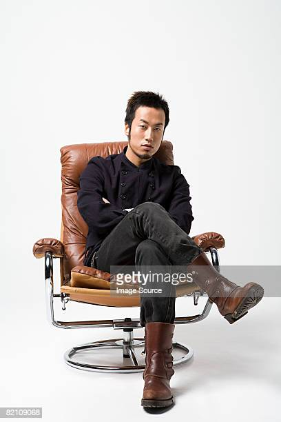 Japanese man sitting on a leather armchair